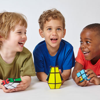three boys holding the Rubik's Junior Range