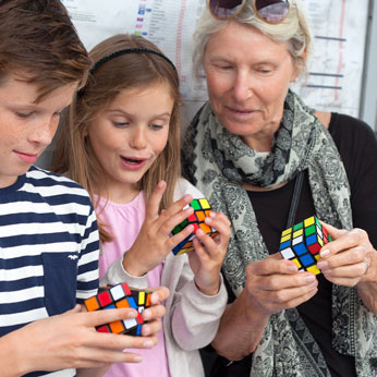 granmother and children solving Rubik's Cube